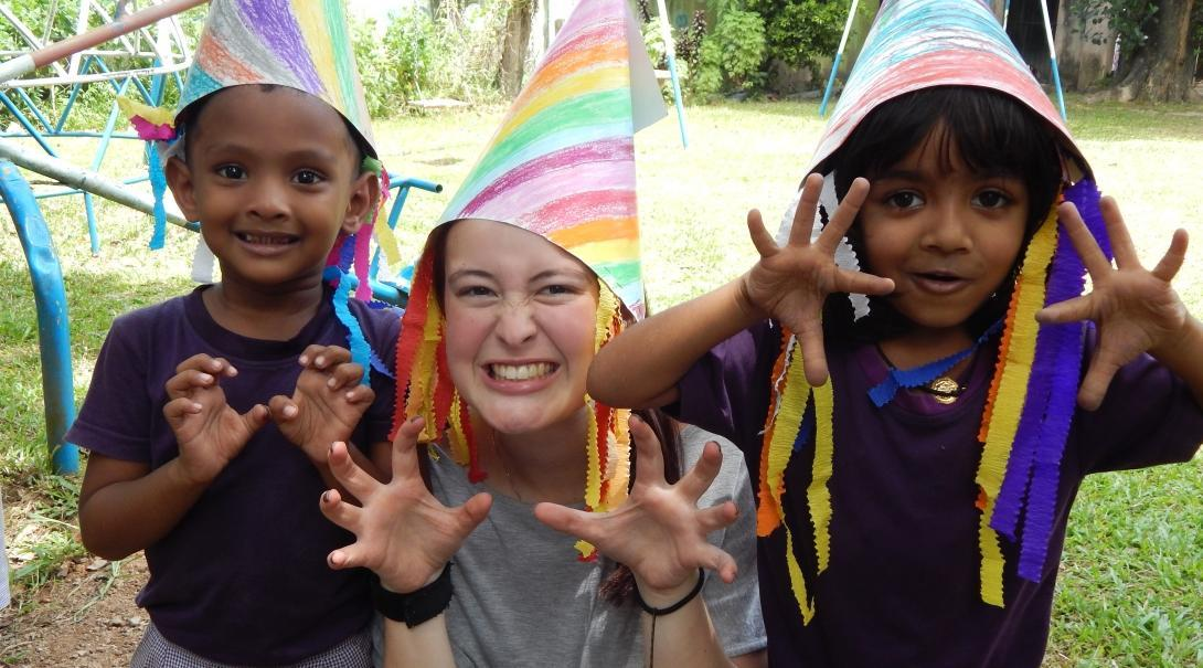 Female Childcare volunteer and children wear hats they have made during a fun activity on a Care placement in Sri Lanka.